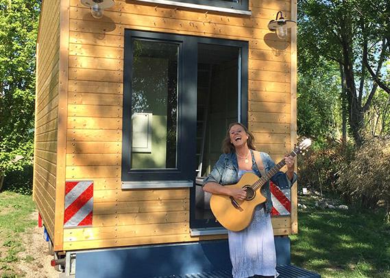 Katrin Grassmann mit Gitarre vor einem Tiny-House