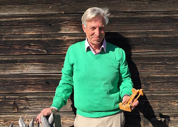 Wolfgang M. Hirscher vor einer Holzwand