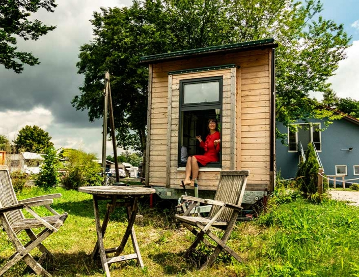 Luise im Tiny House sitzend grünes Gras und Baum Riexploring