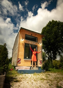 Luise Loue in a red dress standing in frint of her Tiny House Riexploring