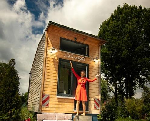 Luise Loué im roten Kleid vor Tiny House Riexploring