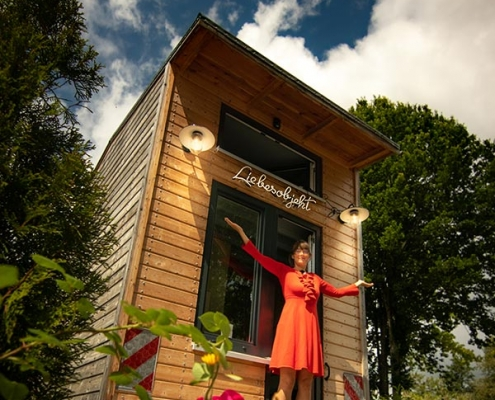 Luise Loue in front of her Tiny House with red dress
